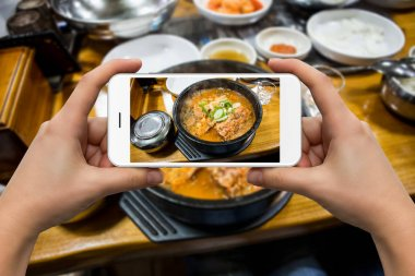 A woman photographs a bowl of soup