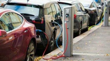 Mnoho elektromobilu jsou účtovány dobíjecích stanic na parkovišti. Kamera se pohybuje vpřed