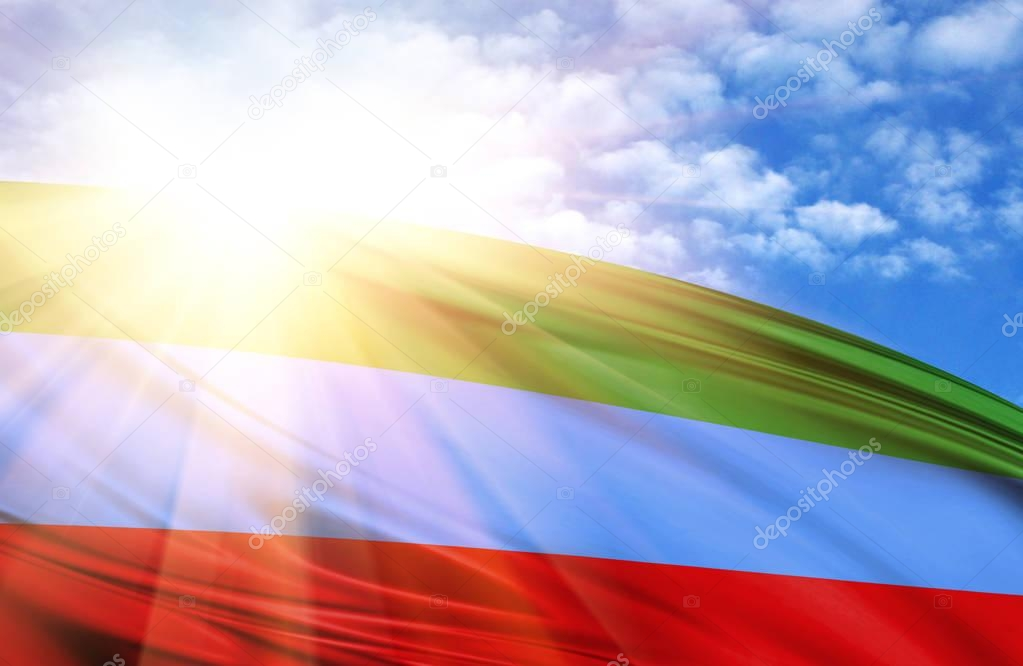 flag of Dagestan against the blue sky with sun rays
