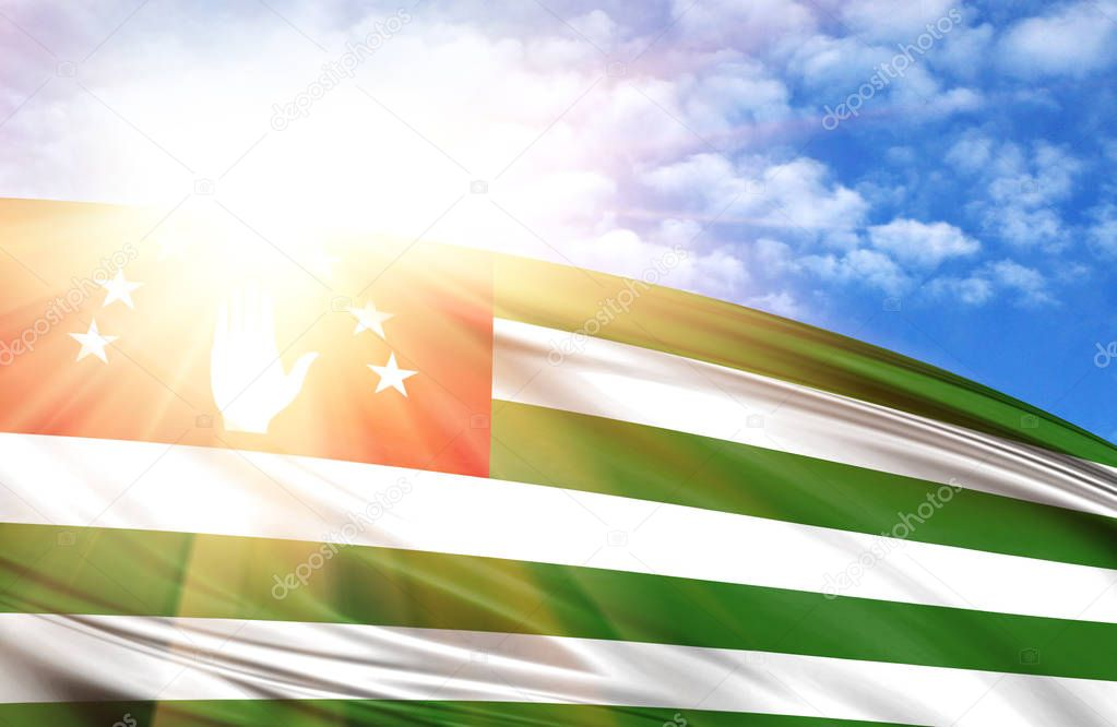 flag of Abkhazia against the blue sky with sun rays