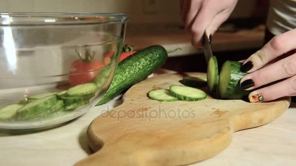 fiatal lány vágás egy uborkát késsel