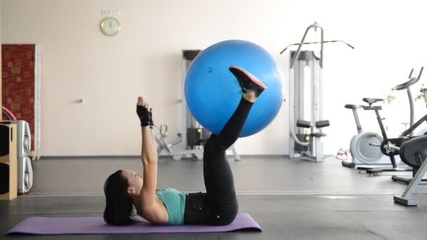 Sportlerin macht Übungen mit Ball am Boden