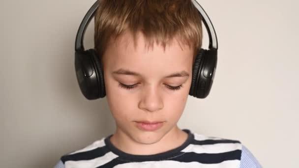 teenage boy texting using smartphone listening to music wearing headphones