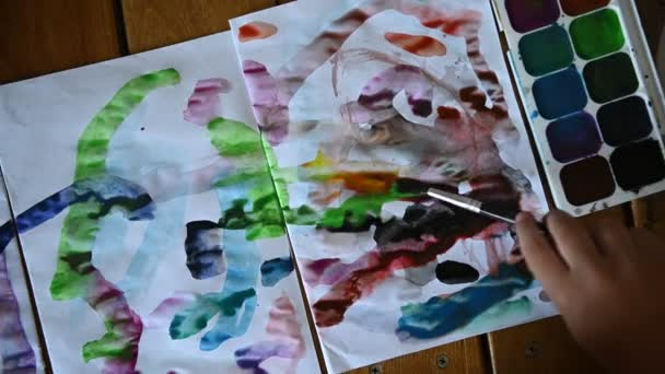 Malý chlapec 4 let kreslí akvarely na bílém prostěradle