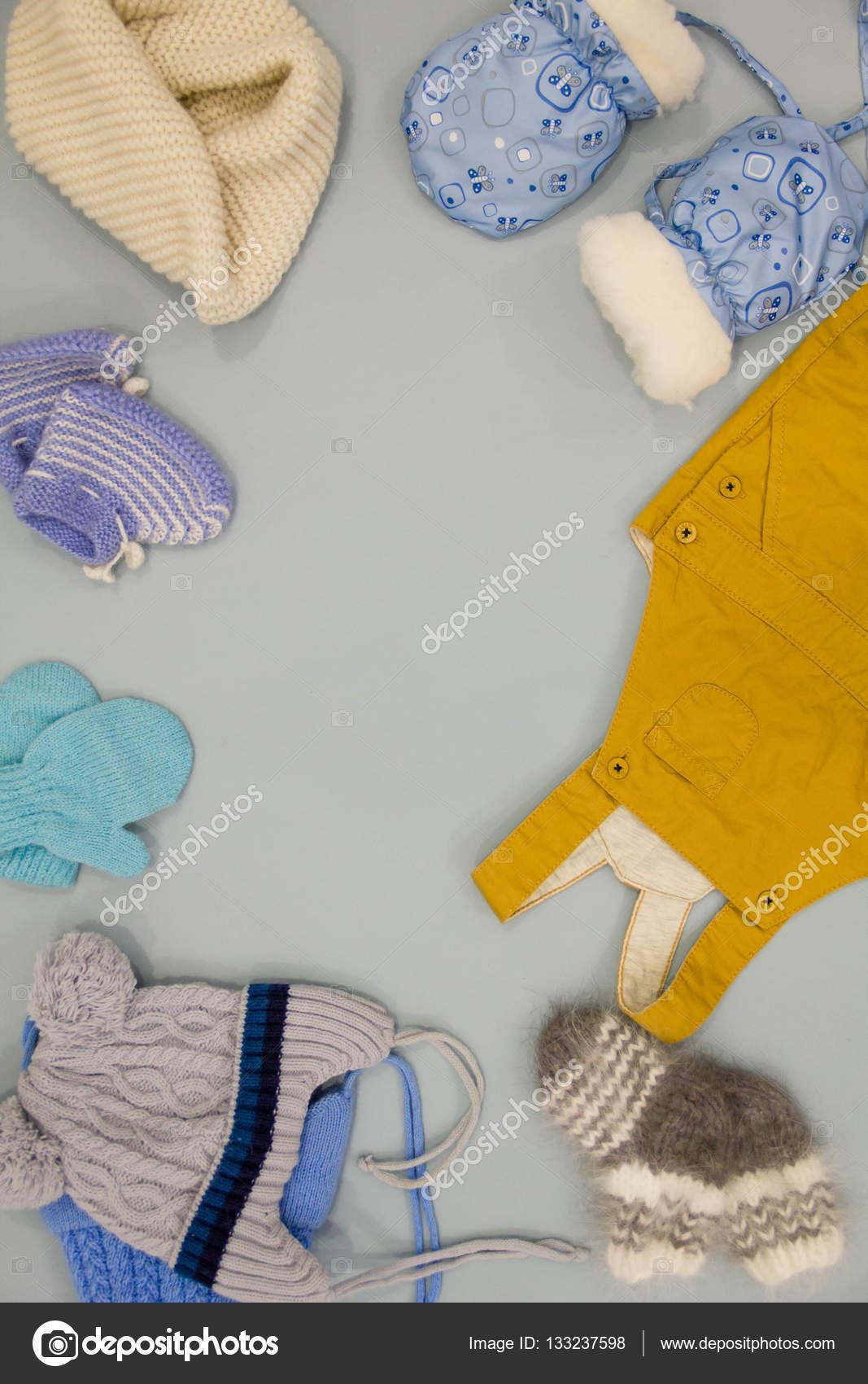 c0c156fe81a1 Σωρός από πλεκτό χειμωνιάτικα ρούχα σε φόντο ξύλινη καλυμμένη με  φθινοπωρινά φύλλα