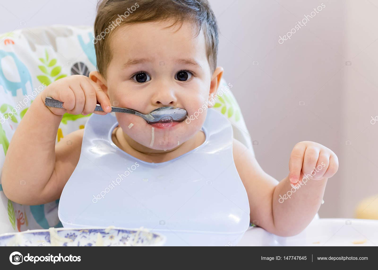 Sonriente Niño Comiendo En La Cocina. 1 Año Bebé Comer