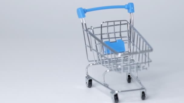shopping toy trolley on white background with some copy space. online shopping concept Closeup Slow motion.
