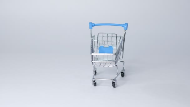 nákupní hračka vozík na bílém pozadí s nějakou kopírovací prostor. online nákupní koncept Closeup Zpomalený pohyb.