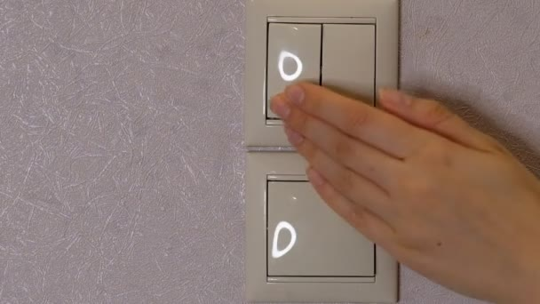 Světlo je vypnuto - ženská ruka vypne tlačítko na světle šedé stěně, přední pohled