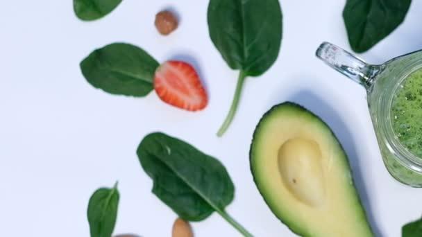 Zdravý Veganský zelený špenátový koktejl. špenát a avokádo na bílém pozadí horní pohled. Uzavření vaření ve zpomaleném filmu