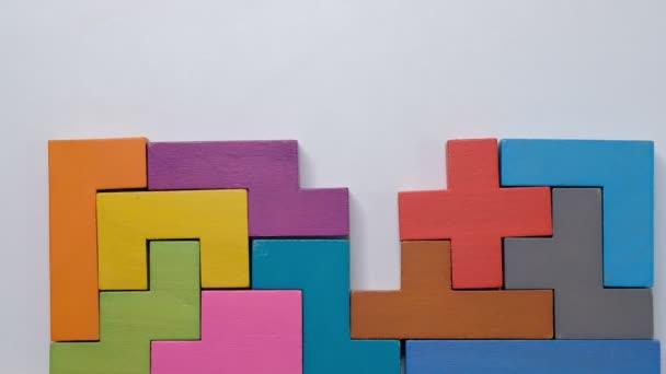 Detailní Zpomalený pohyb. Ruka drží kus dřevěné kostky puzzle. Hromada dřevěných kostek. Koncept komplexního a inteligentního logického myšlení.