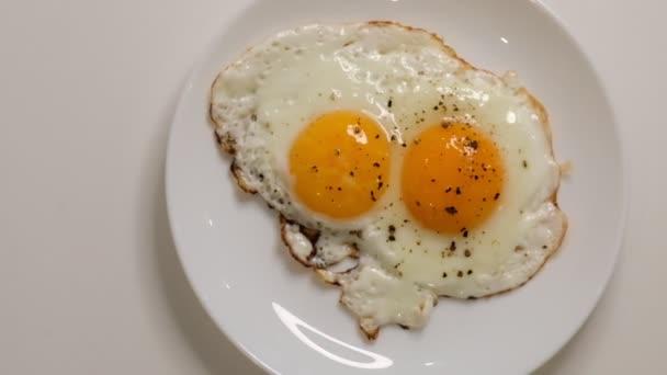 Két tükörtojás tányéron. Tányért sült tojással az asztalra. Zárjuk be a fehér porcelán tányért tükörtojással. Hagyományos reggeli
