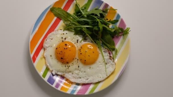 Dvě smažená vejce na talíři. Položit talíř se smaženými vejci na dřevěný stůl. Zblízka bílý porcelánový talíř se smaženým vejcem. Tradiční snídaně