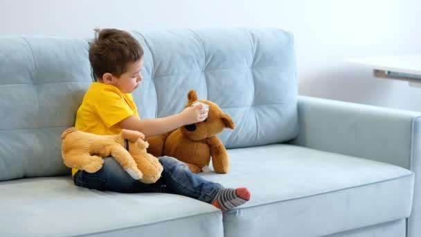videó Portré kisfiúról Teddy macival otthon. baba ölel egy puha játék.