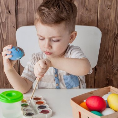Little boy painting colorful eggs for easter on wooden background