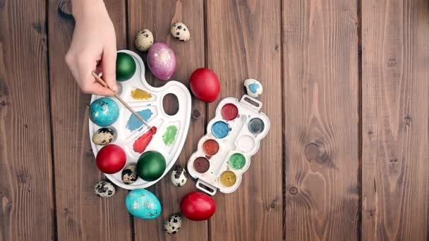 Ručně malované velikonoční vajíčka, barvy a štětce na dřevěném pozadí. Příprava na svátek. Dívčí ruce kreslí vzor.