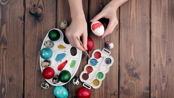 Hand painted Easter eggs, paints and brushes on wooden background. Preparation for the holiday. Girls hands draw a pattern.