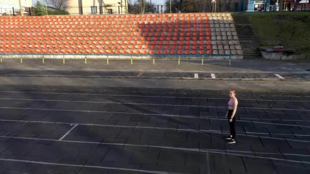 Aerial view of young athletic girl doing sports practice by running on sports track. Sport girl jogging through the stadium