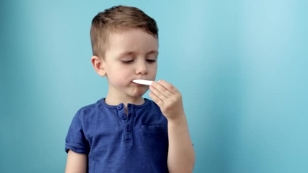 Ill young child with a thermomether, measuring the height of his fever and looking into the camera