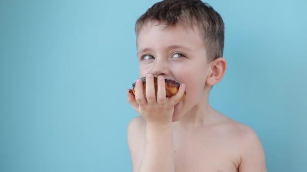Kleiner Junge isst Donut-Schokolade auf blauem Hintergrund. Niedlichen glücklichen Jungen mit Schokolade um den Mund geschmiert. Kinderkonzept, leckeres Essen für Kinder.