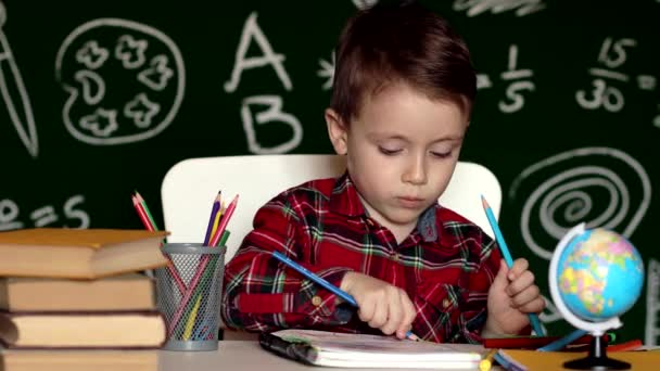 Aranyos kisfiú, aki házi feladatot csinál. Okos gyerek rajzol az asztalnál. Iskolásfiú. Általános iskolás diák rajz a munkahelyen. A kölyök szeret tanulni. Otthoni tanulás. Vissza a suliba. Kisfiú az iskolában.
