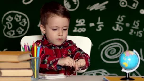 Roztomilý chlapeček, dělá domácí úkoly. Chytrý kluk kreslí za stolem. Školáku. Kreslení žáků základních škol na pracovišti. Kluk se rád učí. Domácí výuka. Zpátky do školy. Malý chlapec ve škole