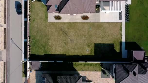 Letecký pohled shora na soukromý dům s dlážděným dvorkem se zeleným trávníkem s betonovou základovou podlahou