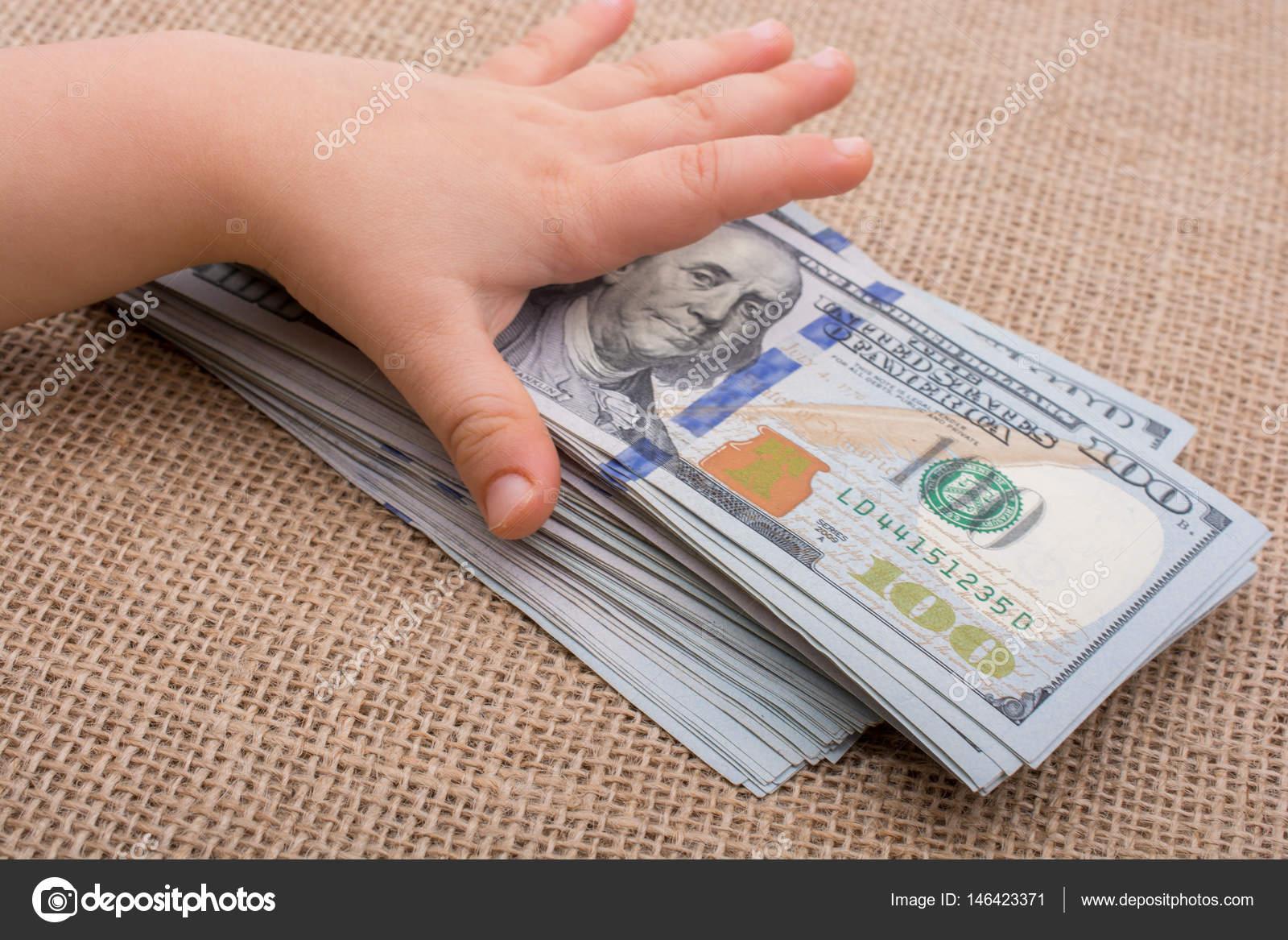 Main de bébé tenant liasse de billets de banque nous dollar dans la main —  Photo a3effb06a27