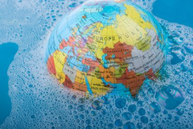 Little model globe floating in blue water covered with foam