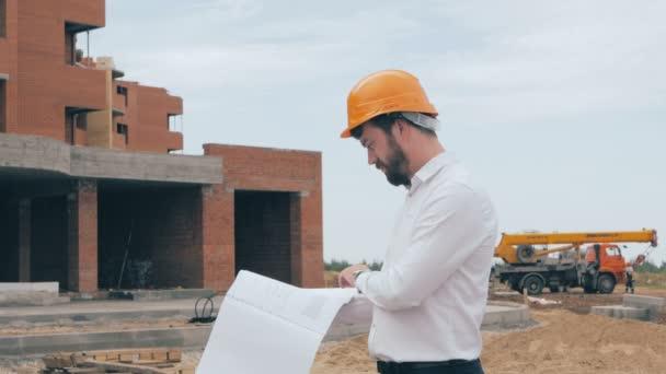 Inženýr se plán na staveništi. Stavitel v přilbu