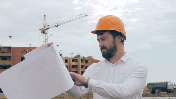 Bauingenieur mit Bauplan arbeitet auf einer Baustelle.