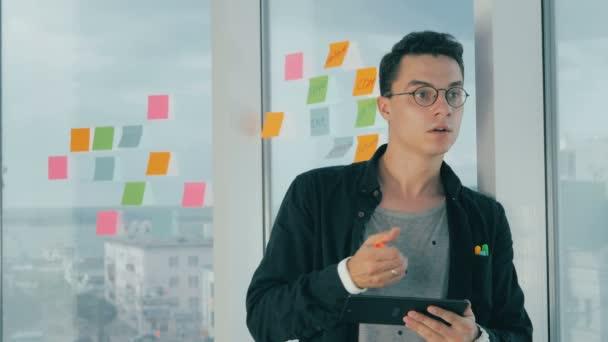Alkalmi fiatal üzletember brainstorming cetlik ablak irodában írásban