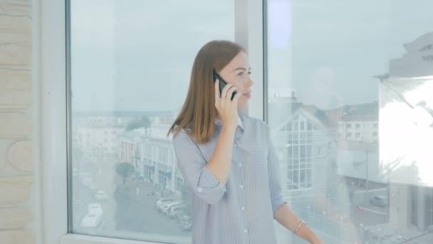 Frau mit Handy im Büro, vor Bürofenstern.