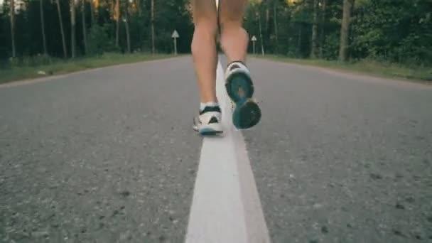 Donna che funziona sulla strada asfaltata, rallentatore