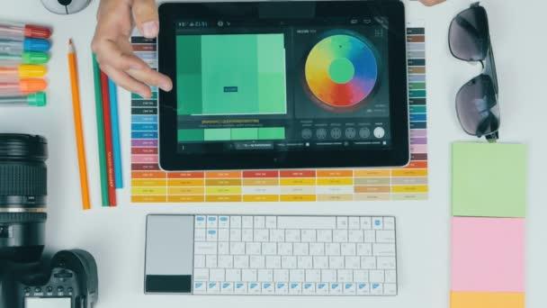 Pohled shora. Malíř, grafik, práce s barvami na stůl z výšky.