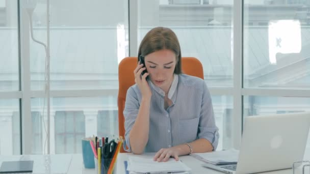 Female receptionist working on computer and talking on the telephone in call center.