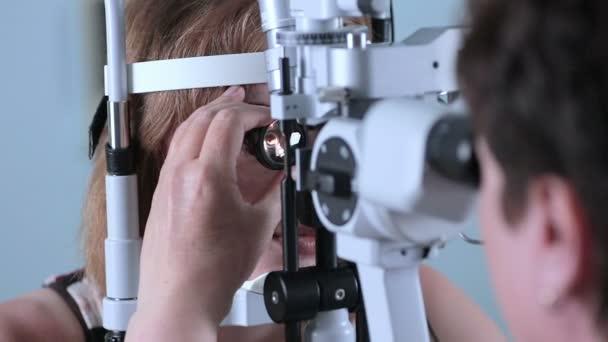 Female Doctor checking eyes with modern medical device. Eye examining at modern hospital.