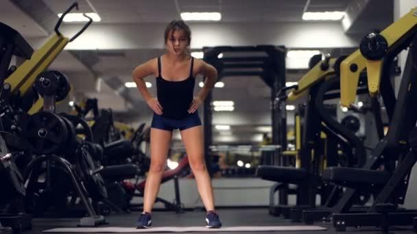 Mladá dívka dělá sportovní cvičení v tělocvičně. Fitness, sport, zdravý životní styl, vzpírání koncepce