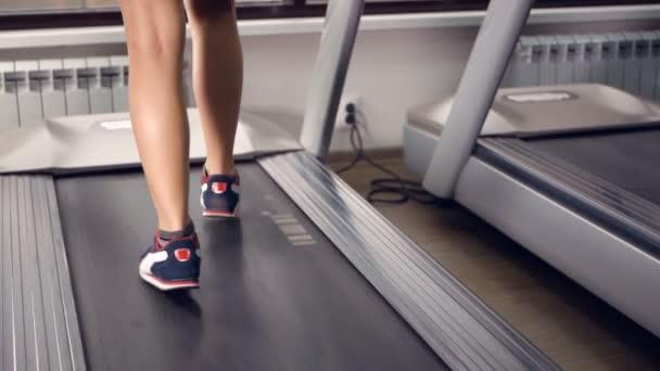 Frauenbeine laufen und laufen auf dem Laufband im Fitnessstudio. gesunder Lebensstil. Zeitlupe.