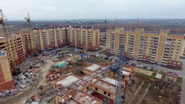 Luftaufnahme der Baustelle. Kamera fliegt in der Nähe der Kran in das neue Gebäude im Bau. Konstruktion und Entwicklung Konzept
