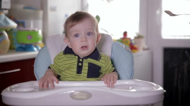 Roztomilé usměvavé dítě jíst, sedí na sedadle dítě doma. Matka, krmení její rozkošný jeden rok starý se lžičkou