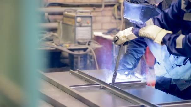 Two welders working. Metalworking plant, welders welding metal.