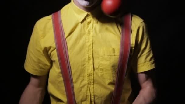 Ijesztő őrült zsonglőr bohóc zsonglőr csapok használata. Szörnyű horror bohóc.