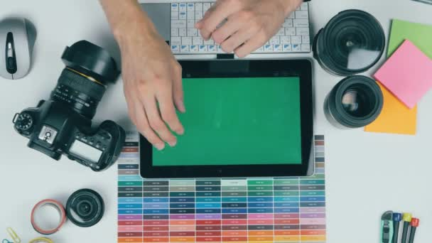 Fotograf, práce s kamerou a laptop u stolu. Pohled shora.