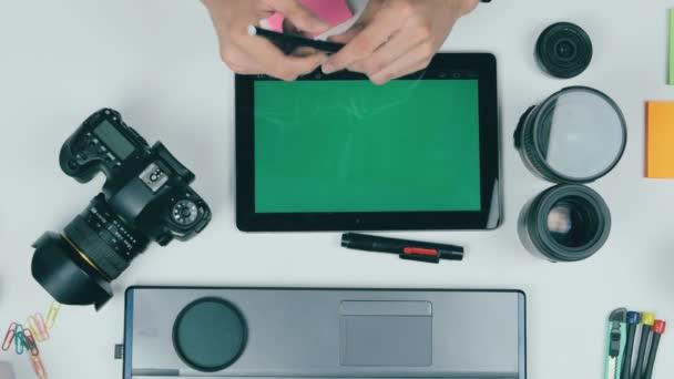 A fotós dolgozik a fényképezőgép és a laptop az íróasztalánál. Nézd meg felülről.