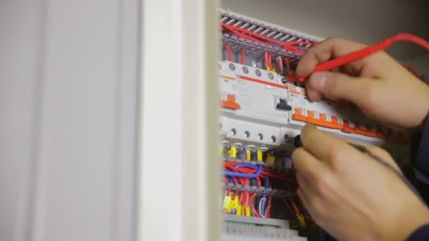 Elektrické pojistky. Elektrikář, přepínání pojistka, jistič v pojistkové skříni a testování.