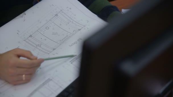 Mužské architekt pracující s plán během hoblování stavební.