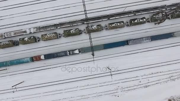 Long freight train coming on the railroad station in winter  Aerial shoot