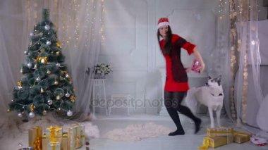Fiatal nő játszik a karácsonyfa közelében kutya