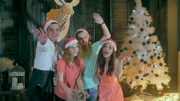 Boldog, vidám baráti karácsonyi partin. Üdvözlés kamerába, szórakozás mosolyogva ünnepli Szilveszter.